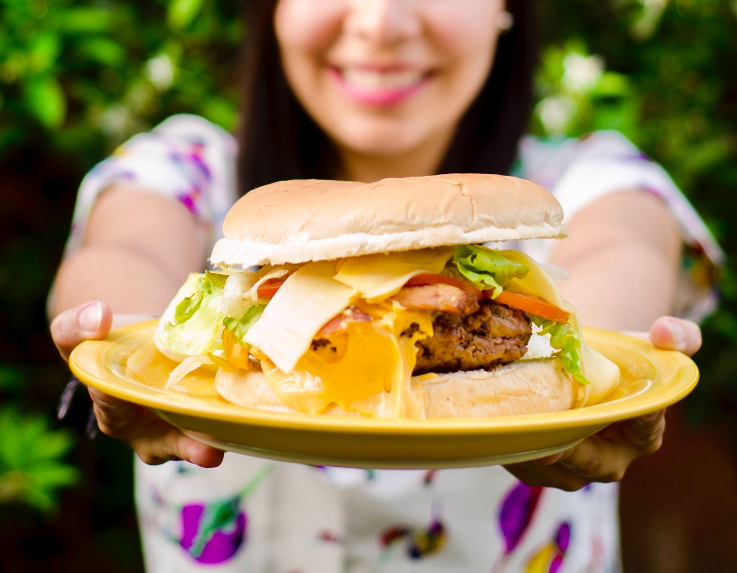 woman serving hamburger cheeseburger smiling