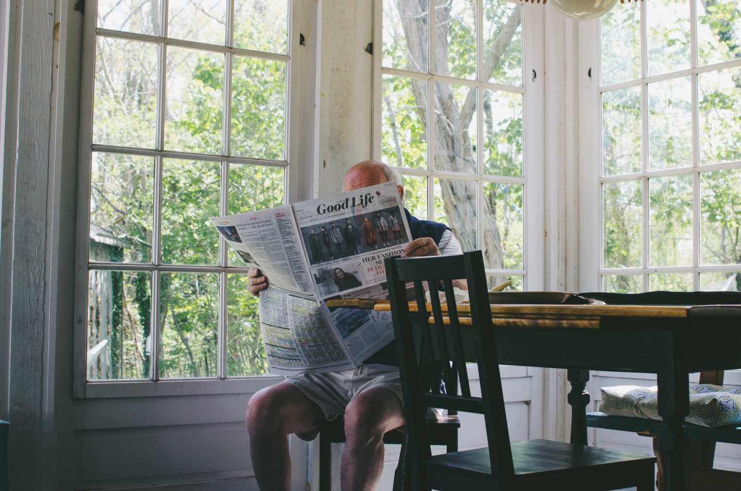 elderly man reading paper at home