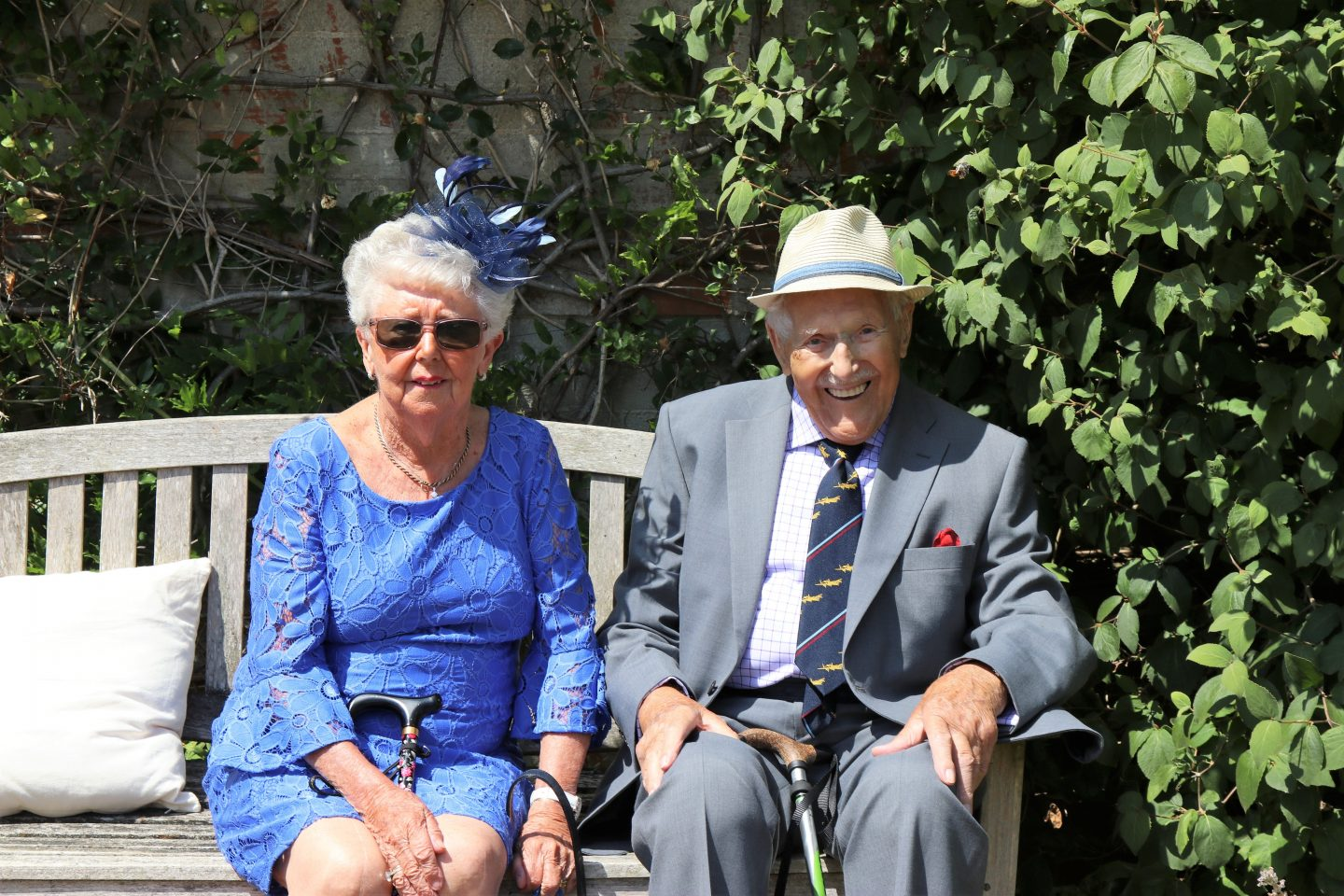 elderly couple sitting on park bench